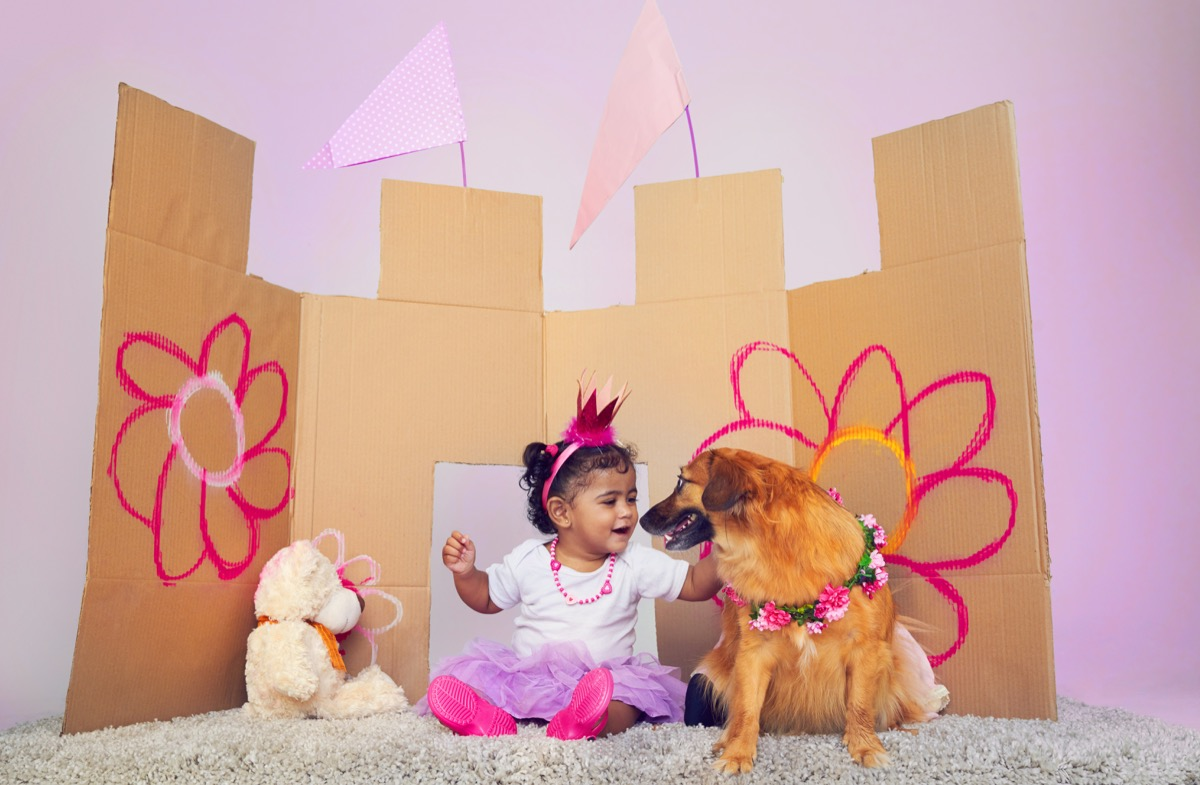 Little girl playing dress up with her dog