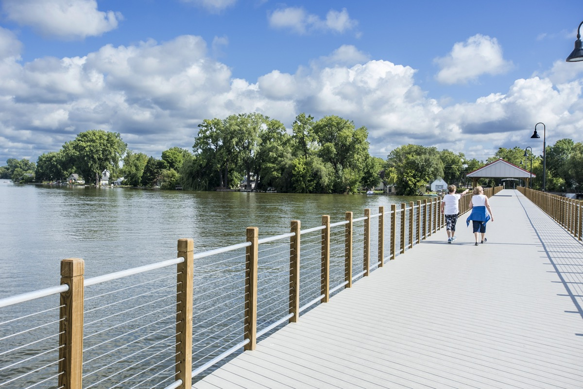 two women walking on a waterfront pathway