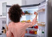 Woman going through refrigerator