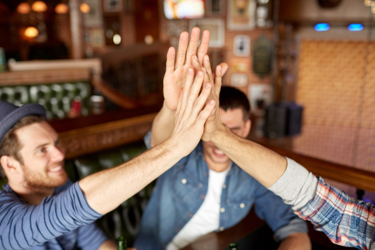 Male friends high-fiving at the bar