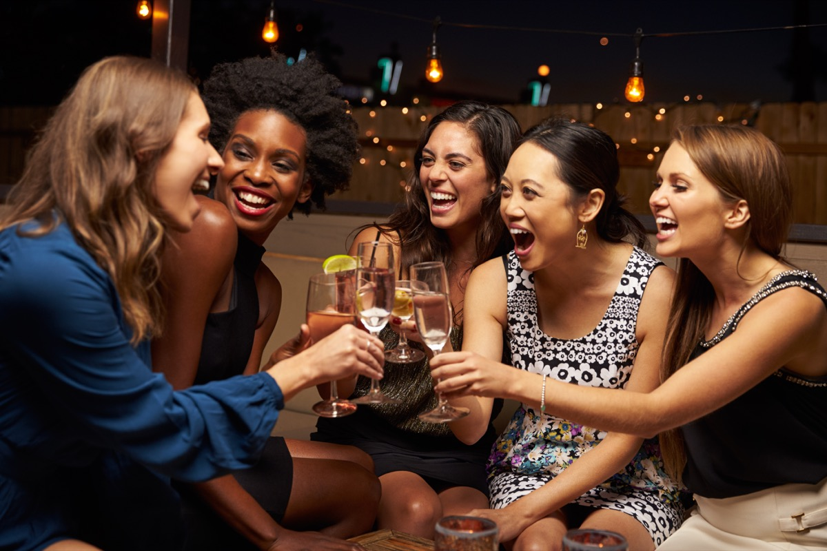 Friends laughing and drinking at a bar
