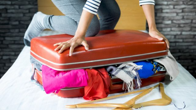 a person tries to close a full suitcase overflowing with clothes