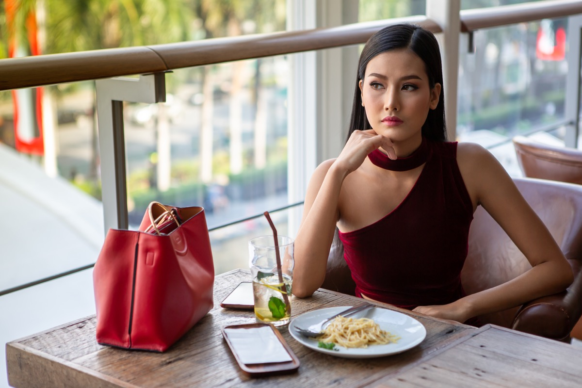 young woman sitting at a lunch place eating alone with the food in front of her, looking sad
