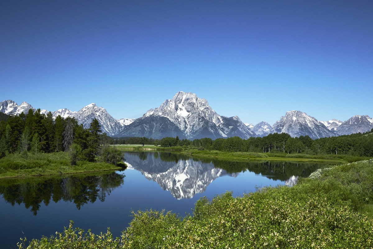 Grand Tetons reflected in still water of the Snake River at Oxbow Bend