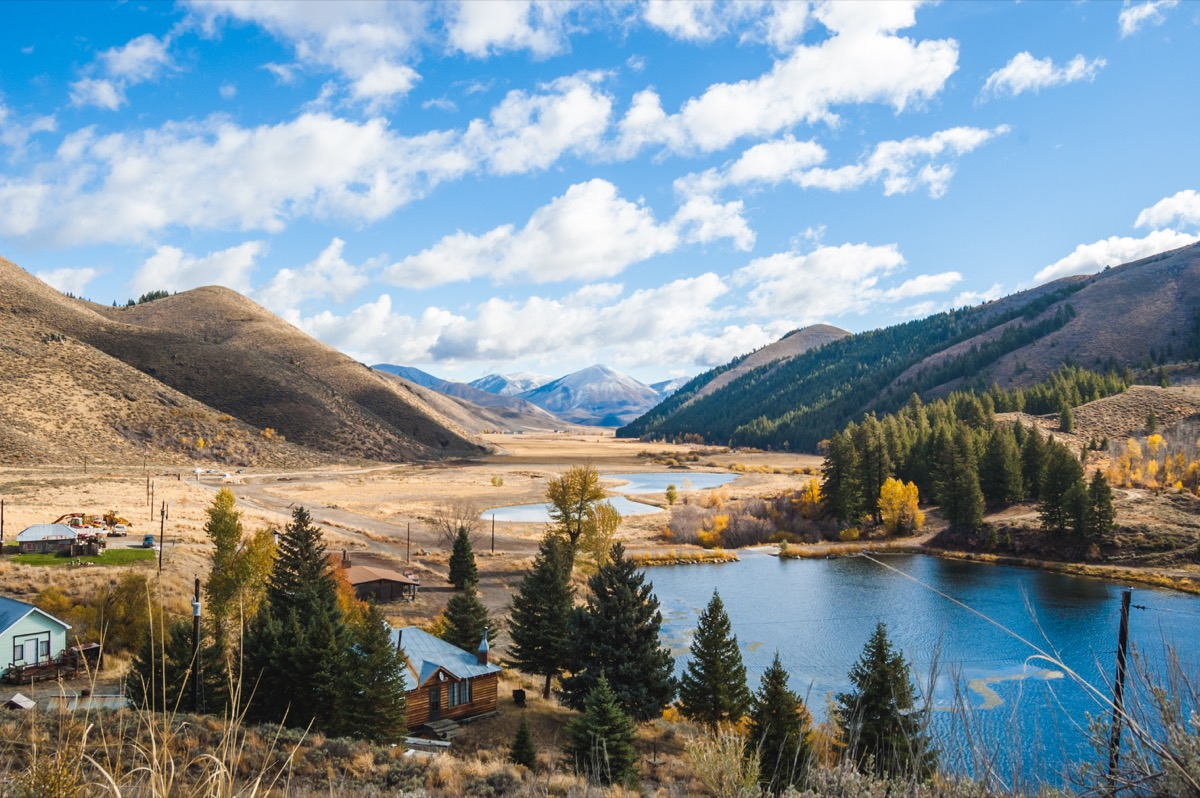 Partly cloudy blue sky over mountain landscape, lake, and countryside properties Deer Creek in Hailey Idaho