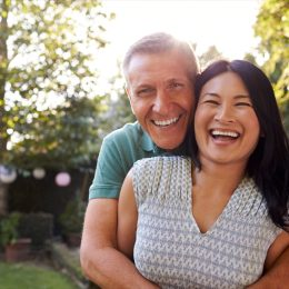 happy middle aged asian woman and white man outdoors