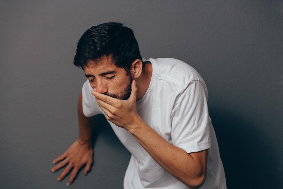 young hispanic man throwing up