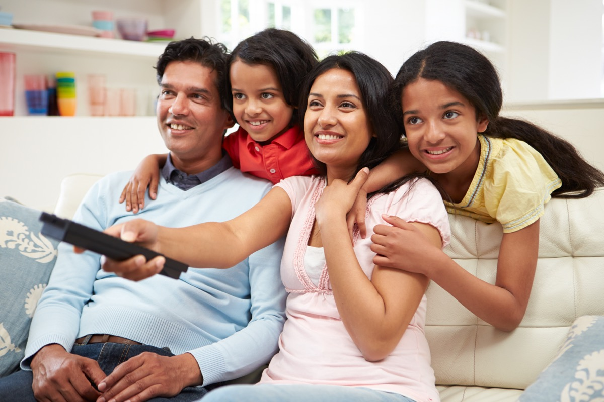 indian family watching tv on couch