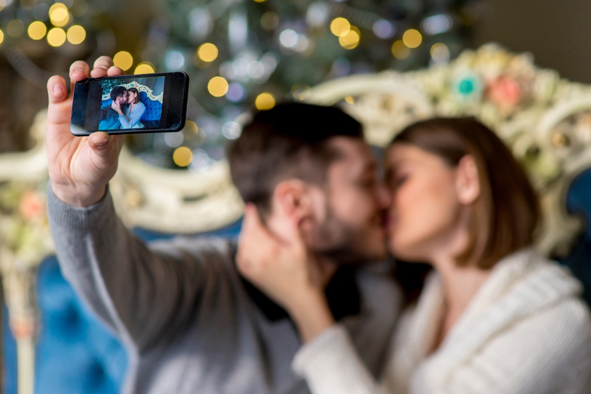 30-something white couple kissing and taking selfie