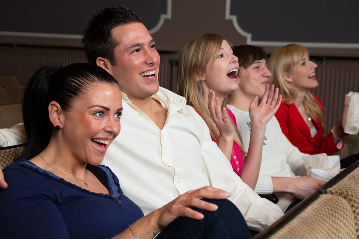 Family laughing in audience of a comedy show