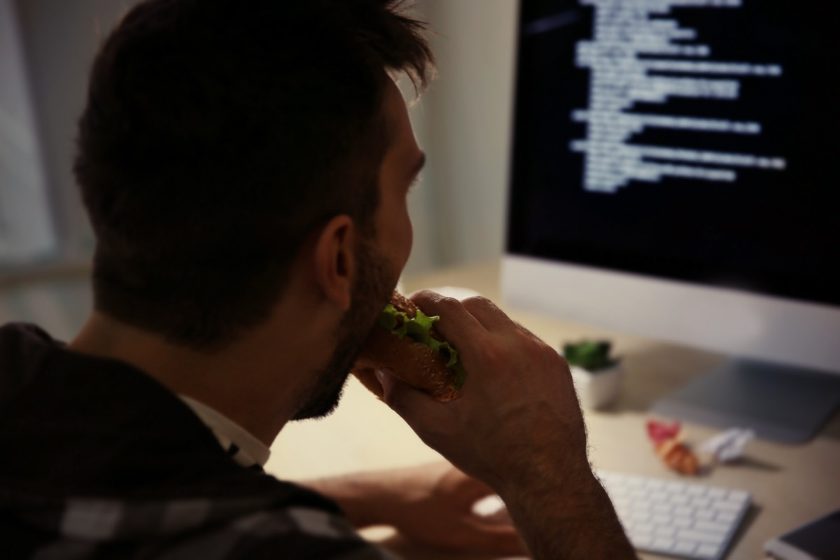 white guy eating in front of computer at night