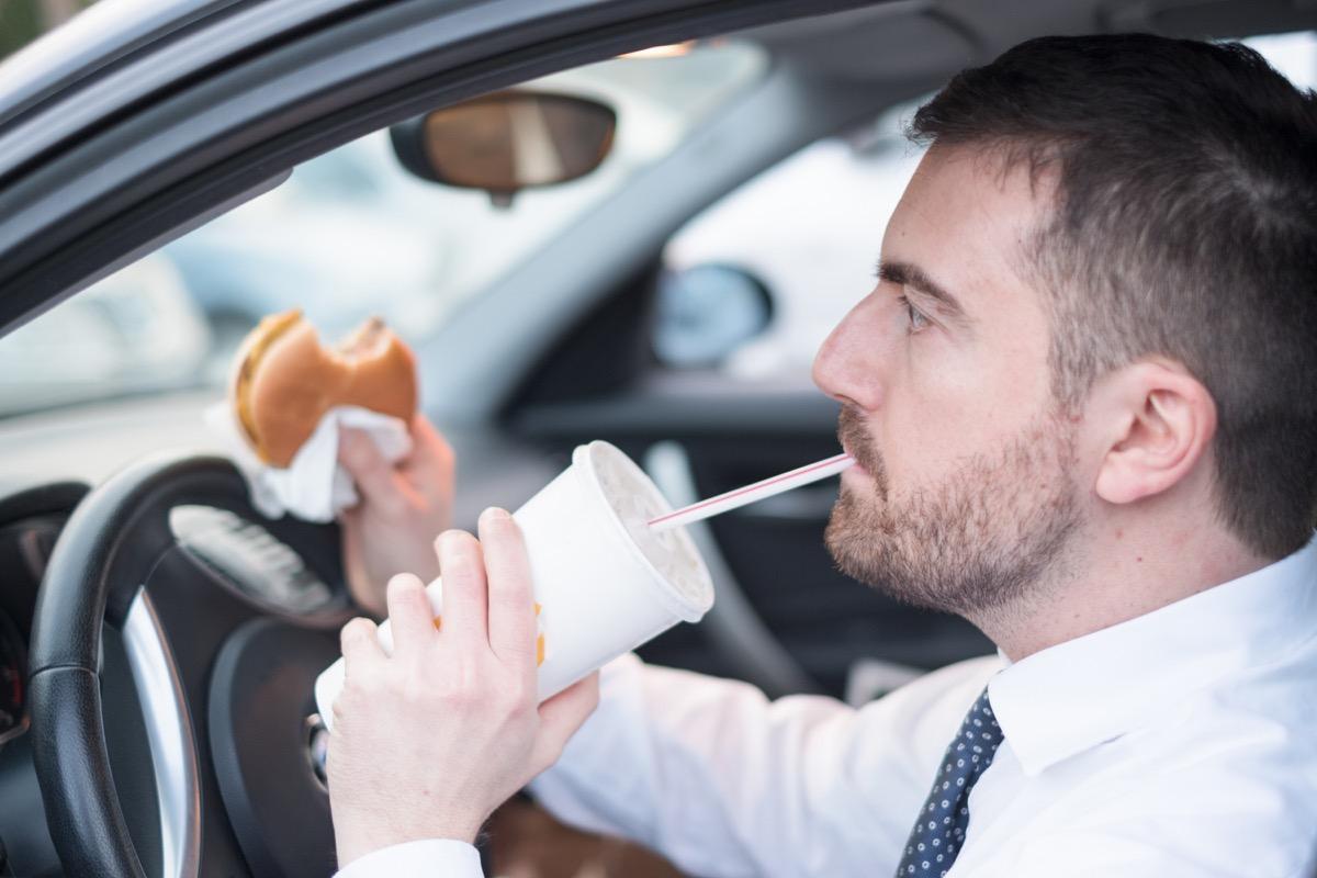 30 something white man eating fast food in car