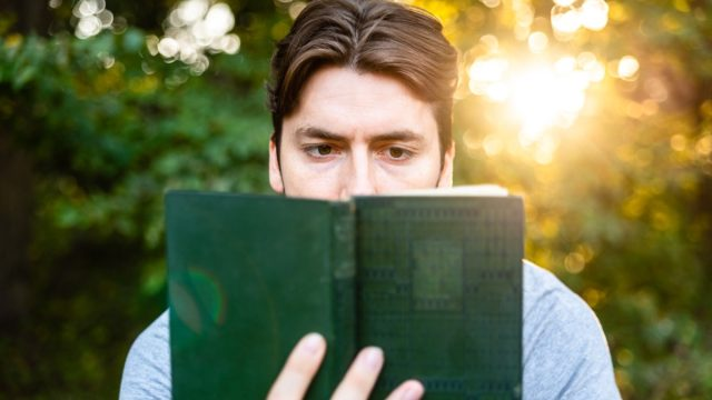 man reads in amazement at an old book about adventures, imagination and literature.