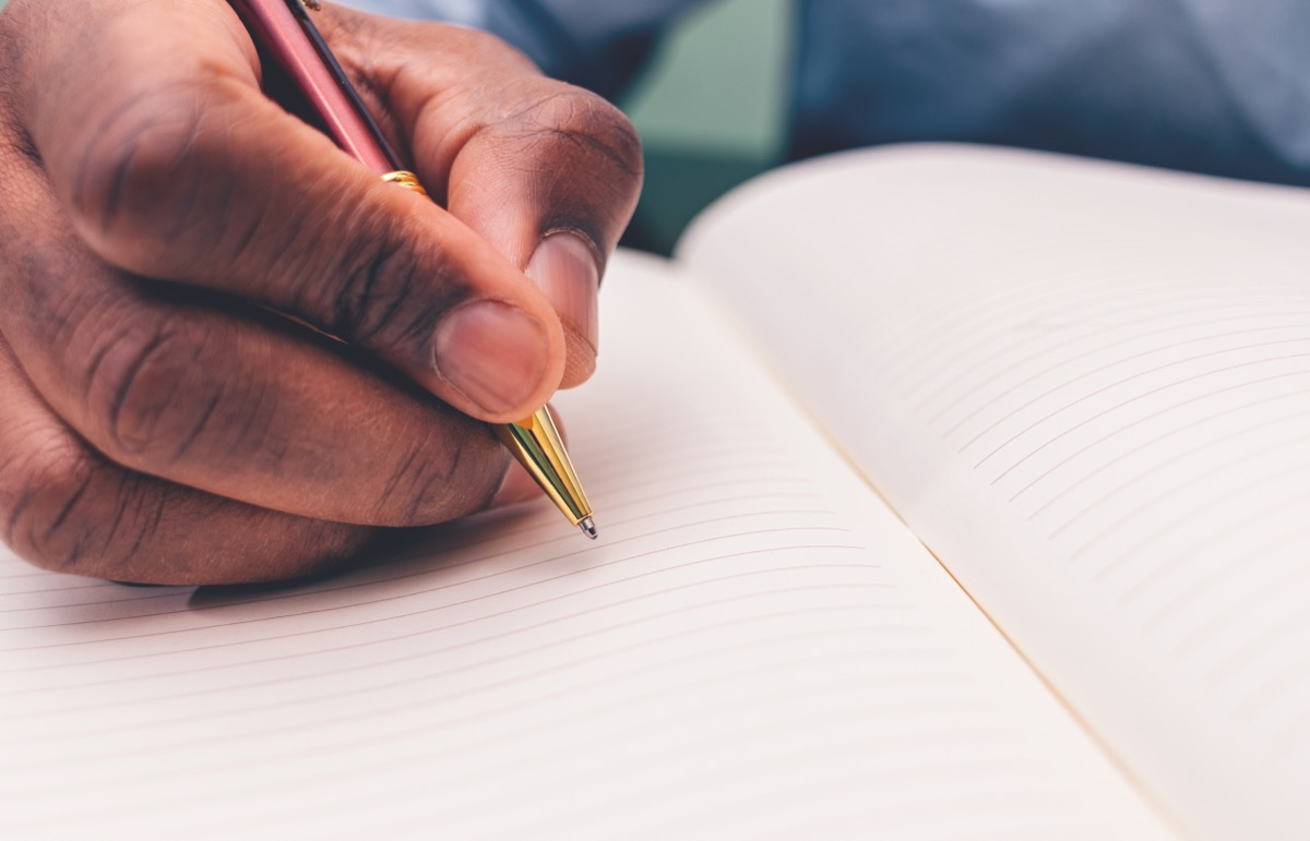 Black man writing in a notebook