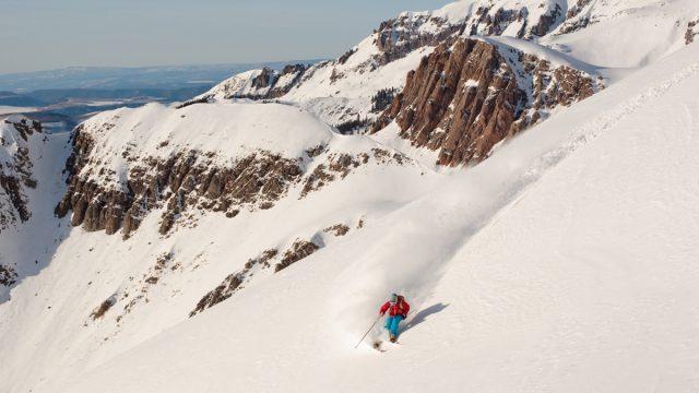 man skiing down untouched snow in Utah
