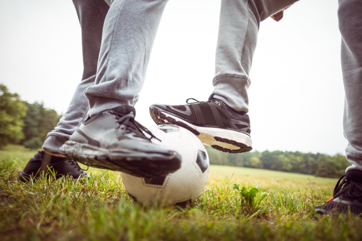 two men playing soccer in gray sweatpants on grass