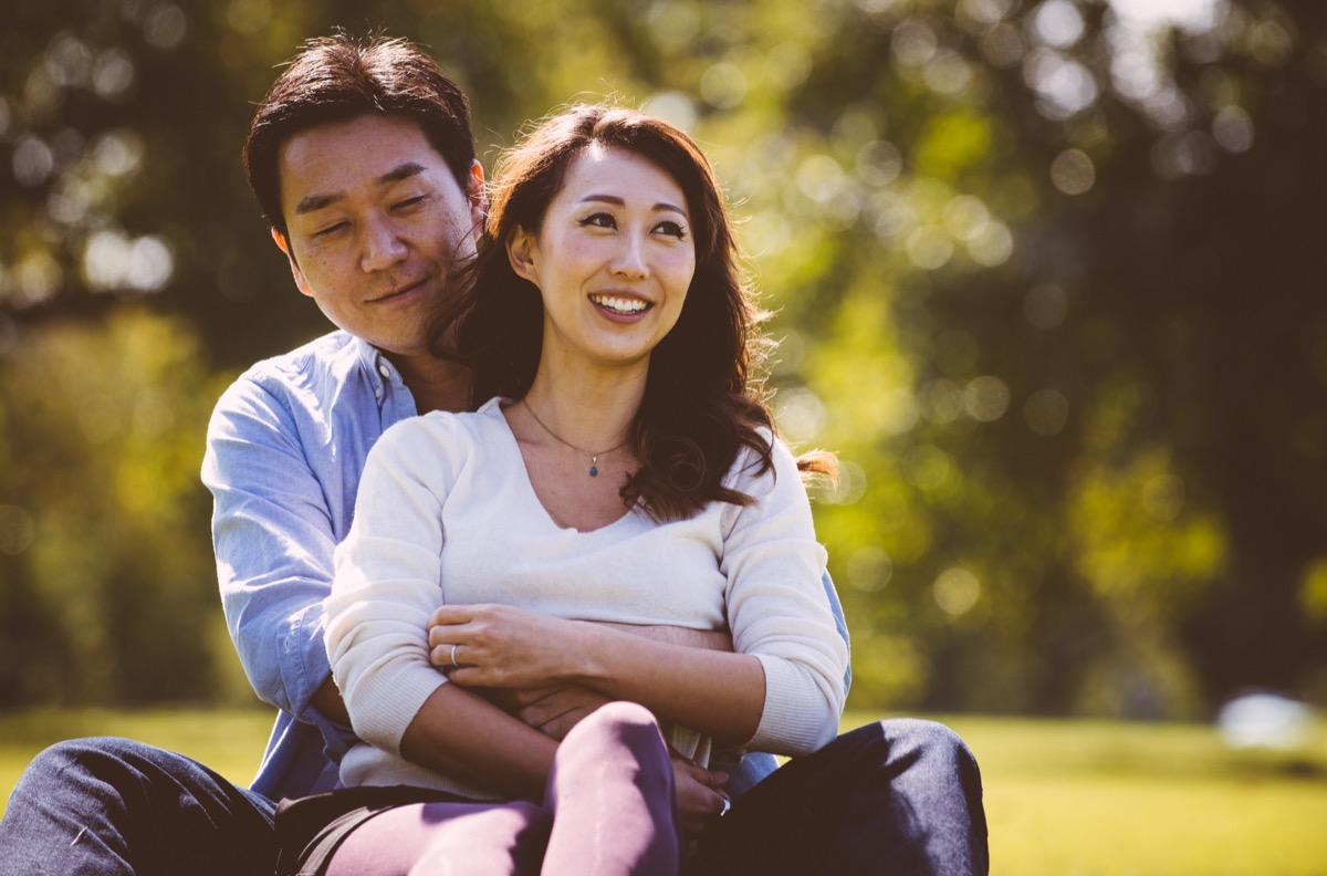 middle aged asian couple sitting in grass