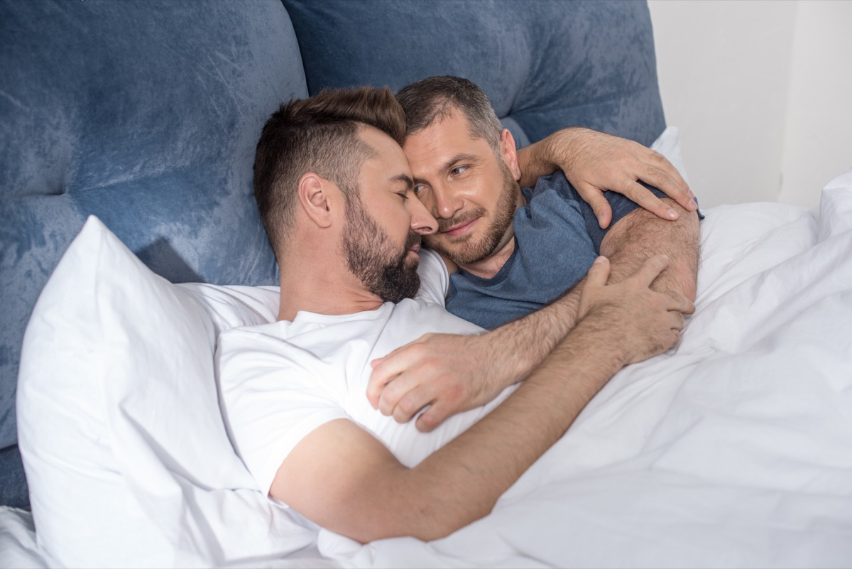 middle aged gay couple cuddling in bed
