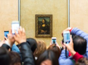 people trying to take a picture of the mona lisa