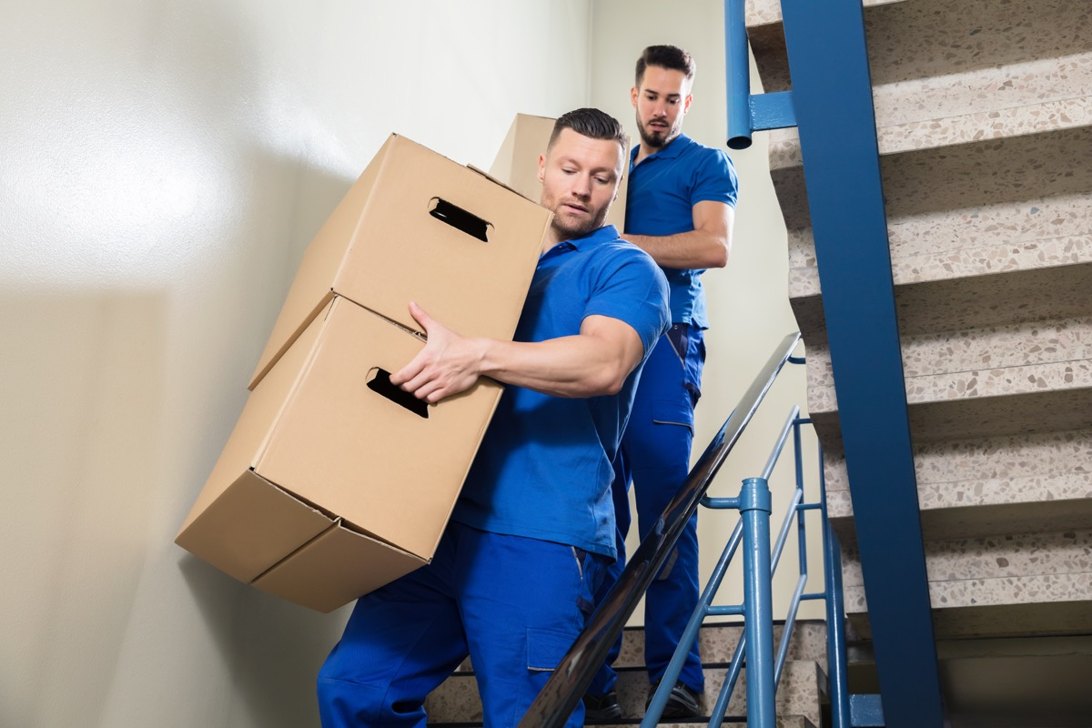 Movers carrying boxes down the stairs