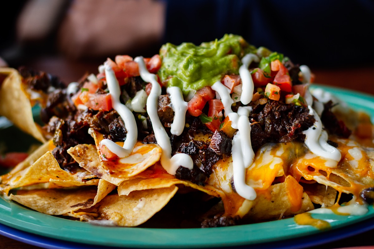 Beef and cheese corn nachos served on a big plate ready to eat - Image