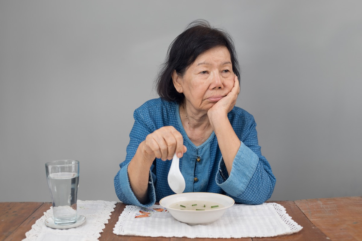 older asian woman refusing a bowl of soup