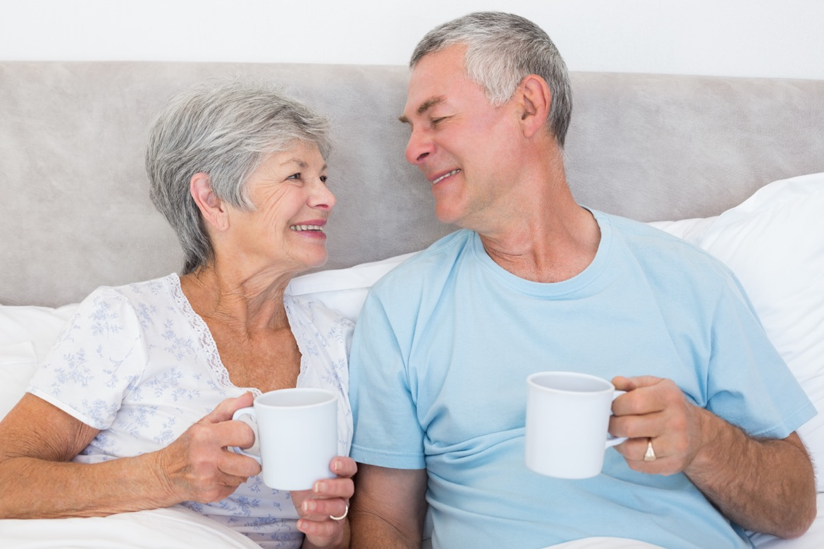 older white straight couple drinking coffee in bed