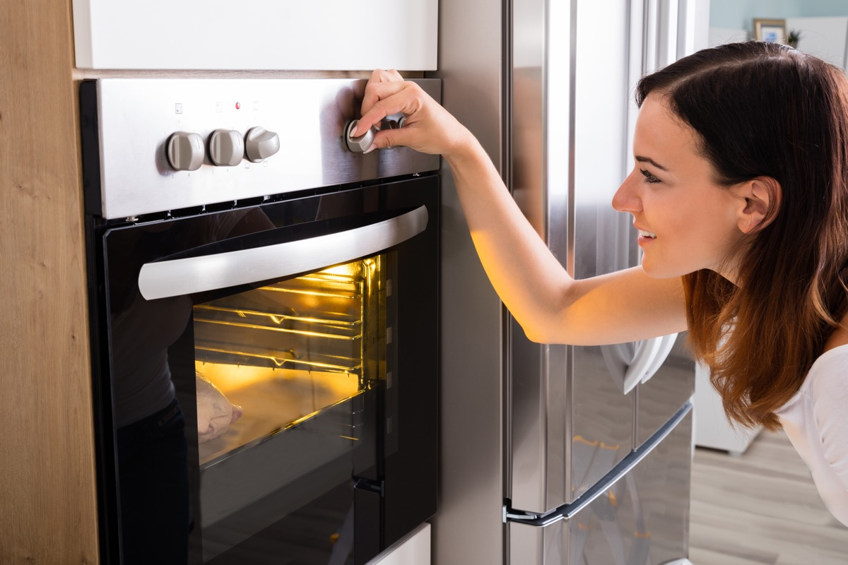 Woman turning dial on oven while cooking
