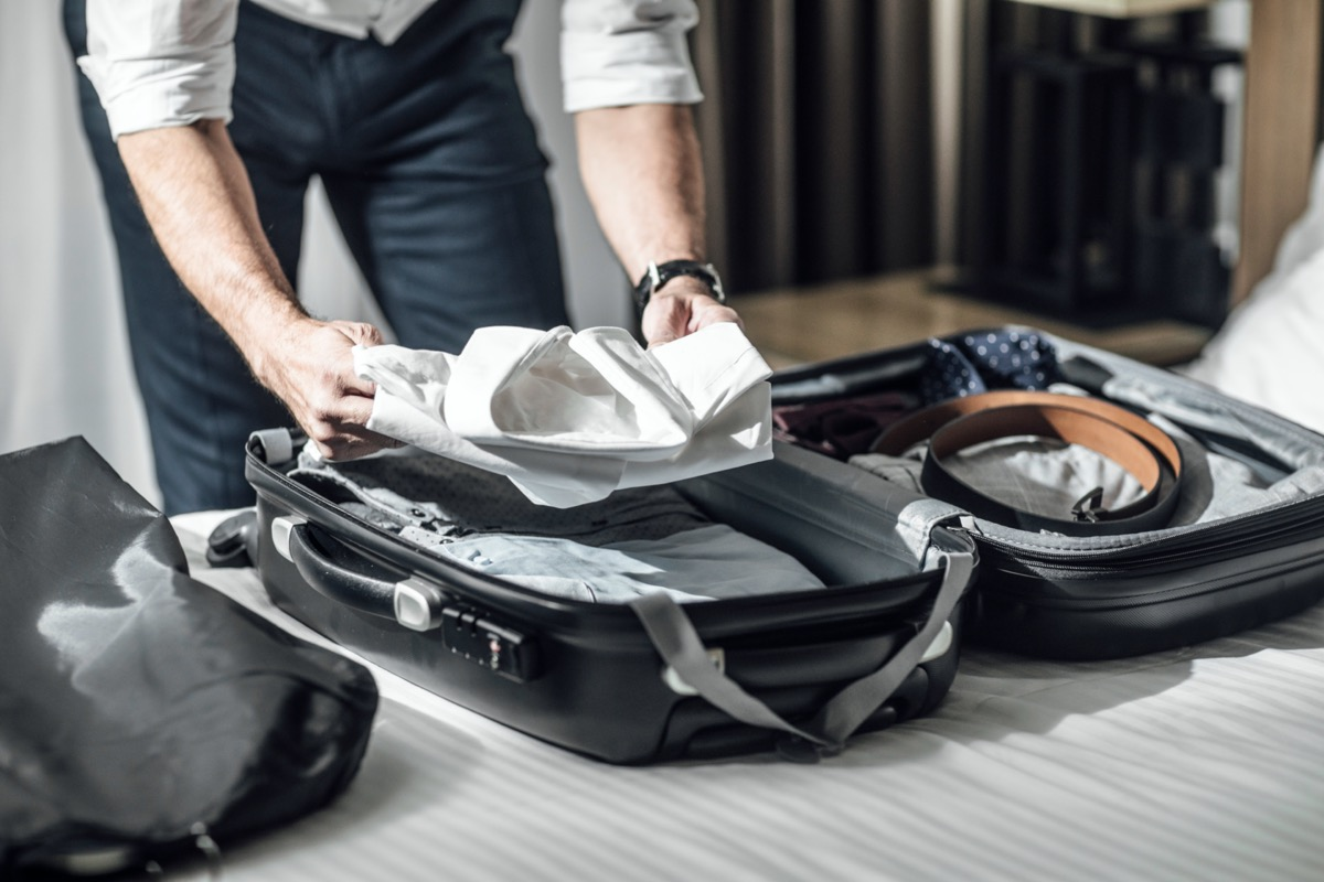 man packing his shirt into a suitcase