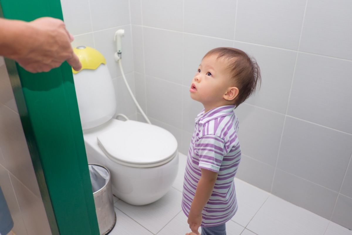 parent's hand on door opening bathroom to tell son to use toilet