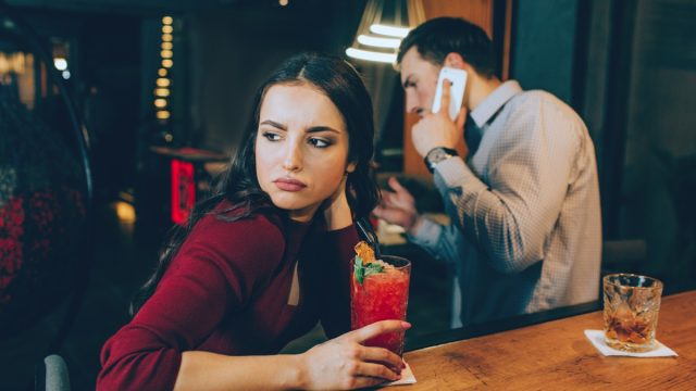 sad girl looking off while her date is on the phone at the bar