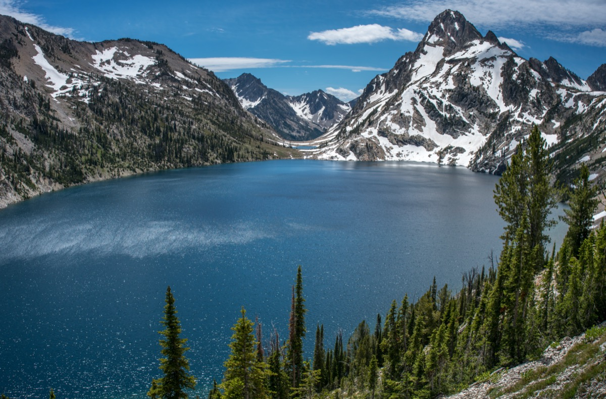 Sawtooth Lake in Idaho wilderness framed with pine trees and rugged snow capped mountain peaks