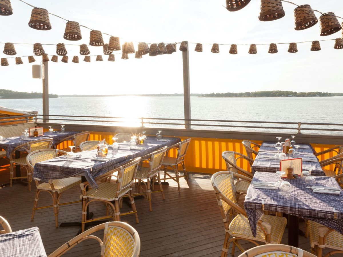 waterfront deck with tables and hanging lights