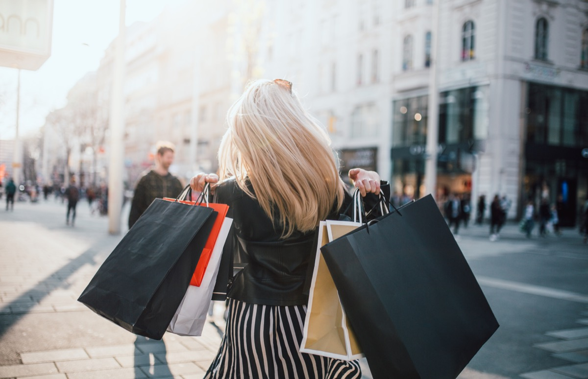 girl walking from store with a lot of shopping bags with back turned to camera
