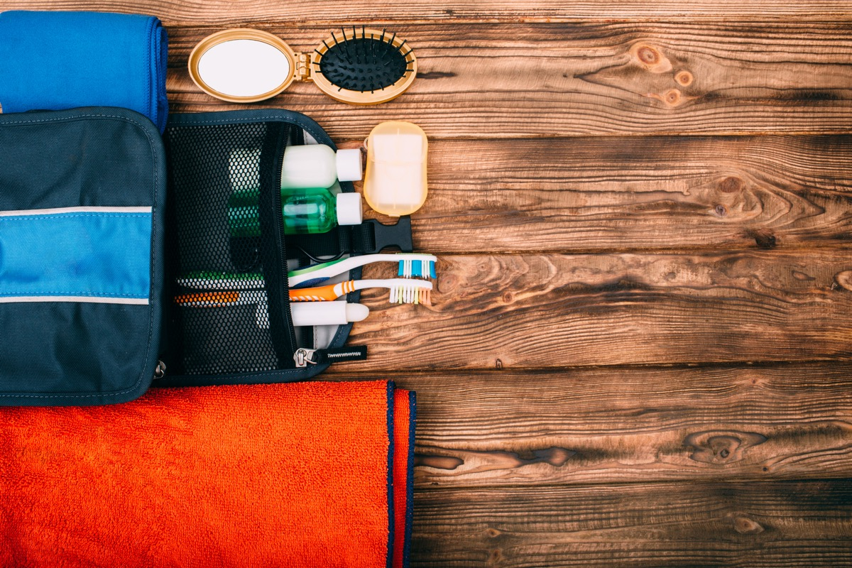 Top view of kit for hygiene during hiking and travel on wooden table with empty space. Items include towel, comb, soap, toothbrushes, shampoo.