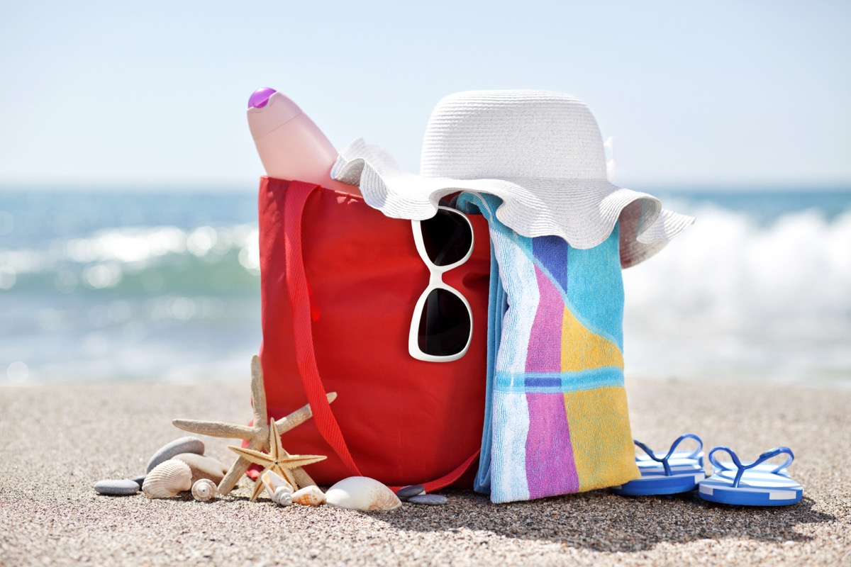 beach bag with hat,towel, sunglasses, sun lotion, pebbles, seashells and flip flops at the beach