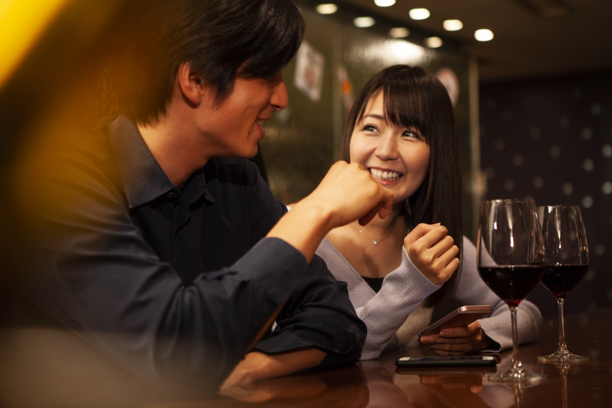 two people on a first date talking over a glass of wine