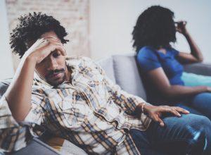 upset 30-something black couple on couch