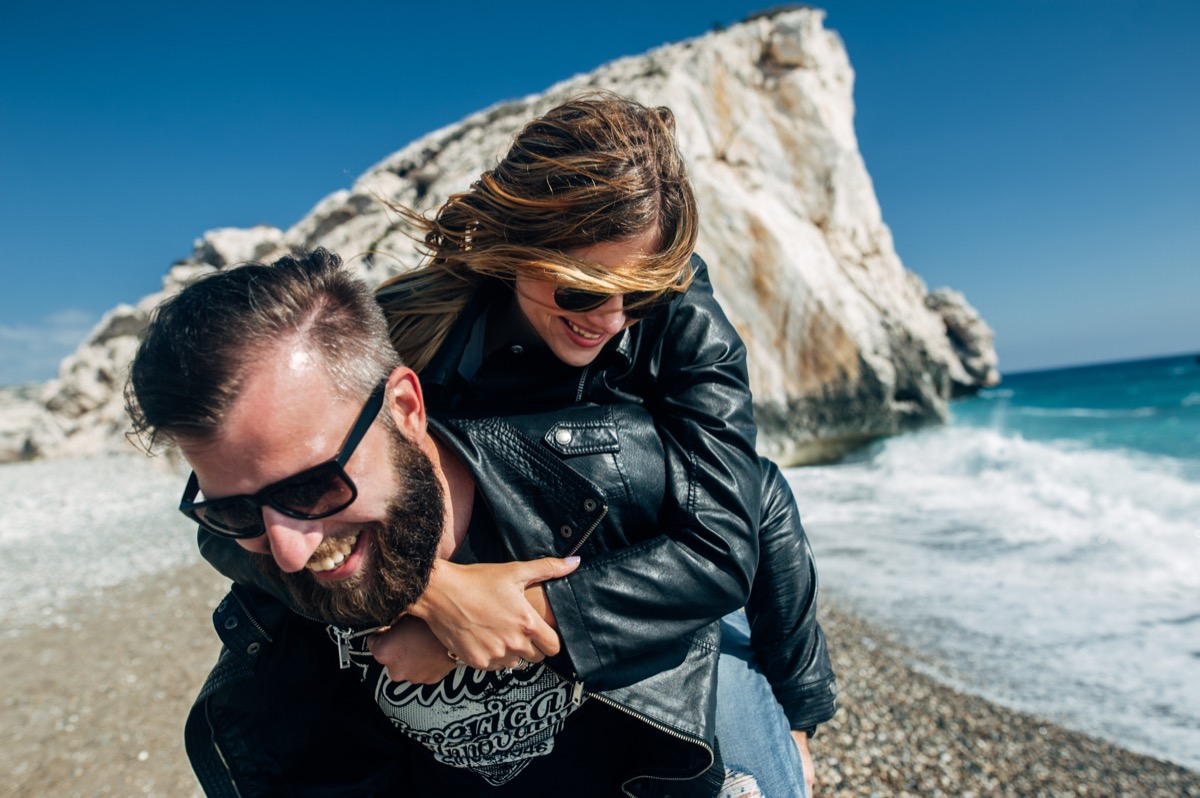 30 something white man and woman wearing leather jackets on the beach