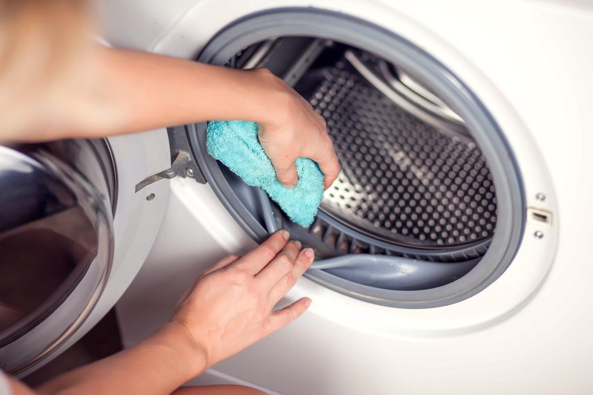 woman's hand wiping down inside of washing machine