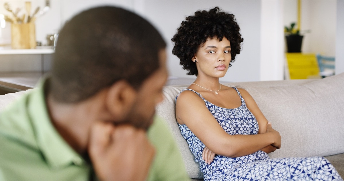 woman staring angrily at her partner while sitting on the couch
