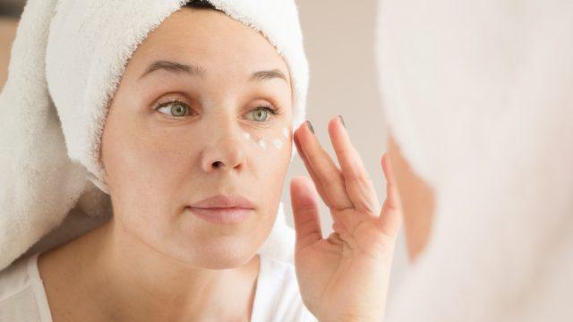 middle-aged white woman applying eye cream