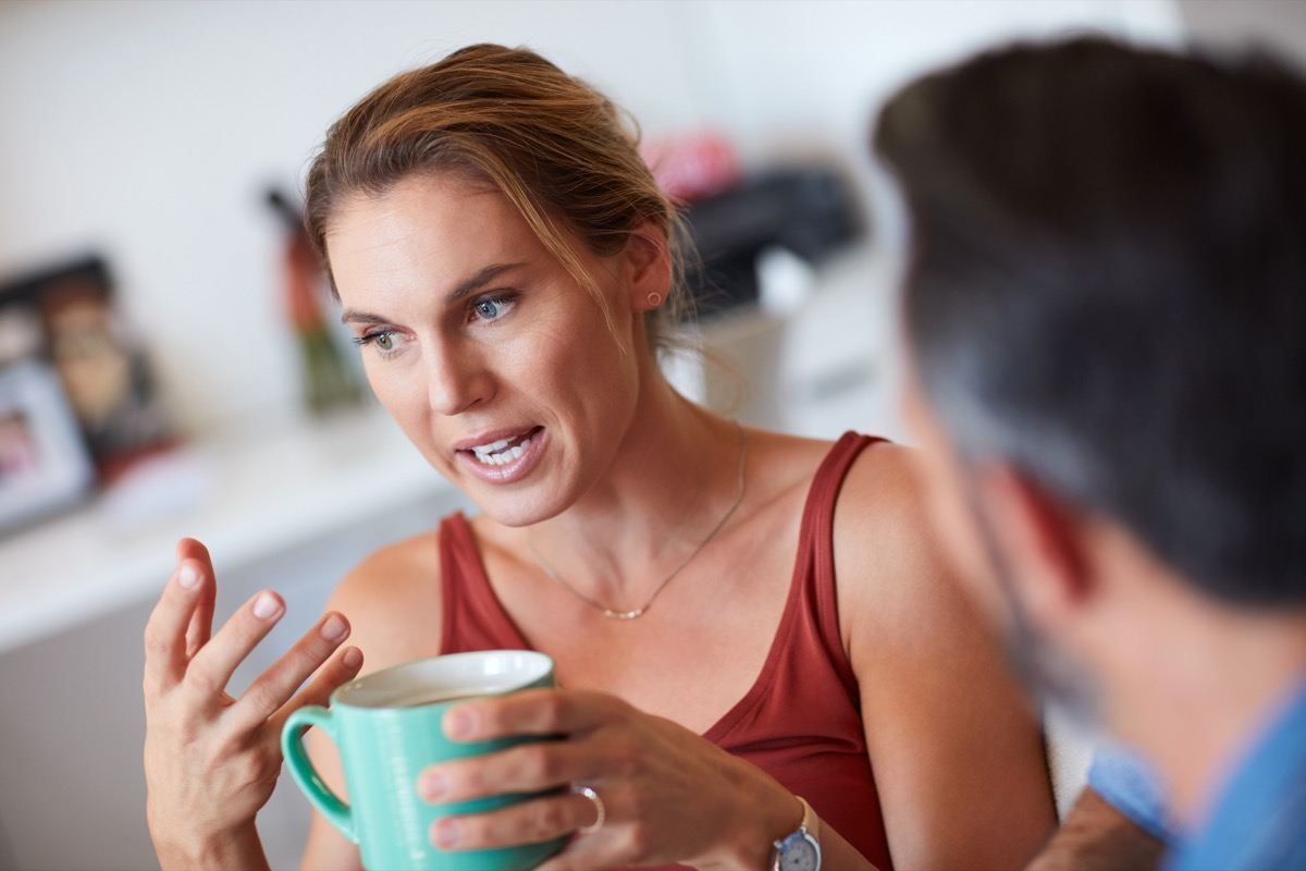 cropped shot of a woman asking a man questions over a cup of coffee