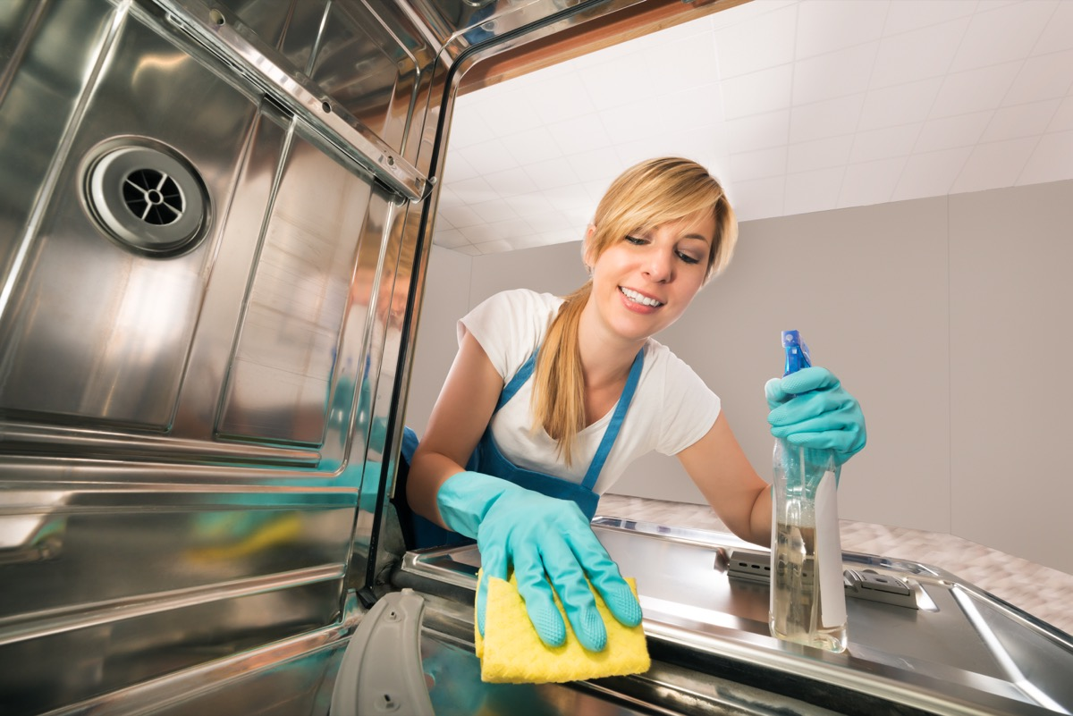 Woman cleaning a dishwasher