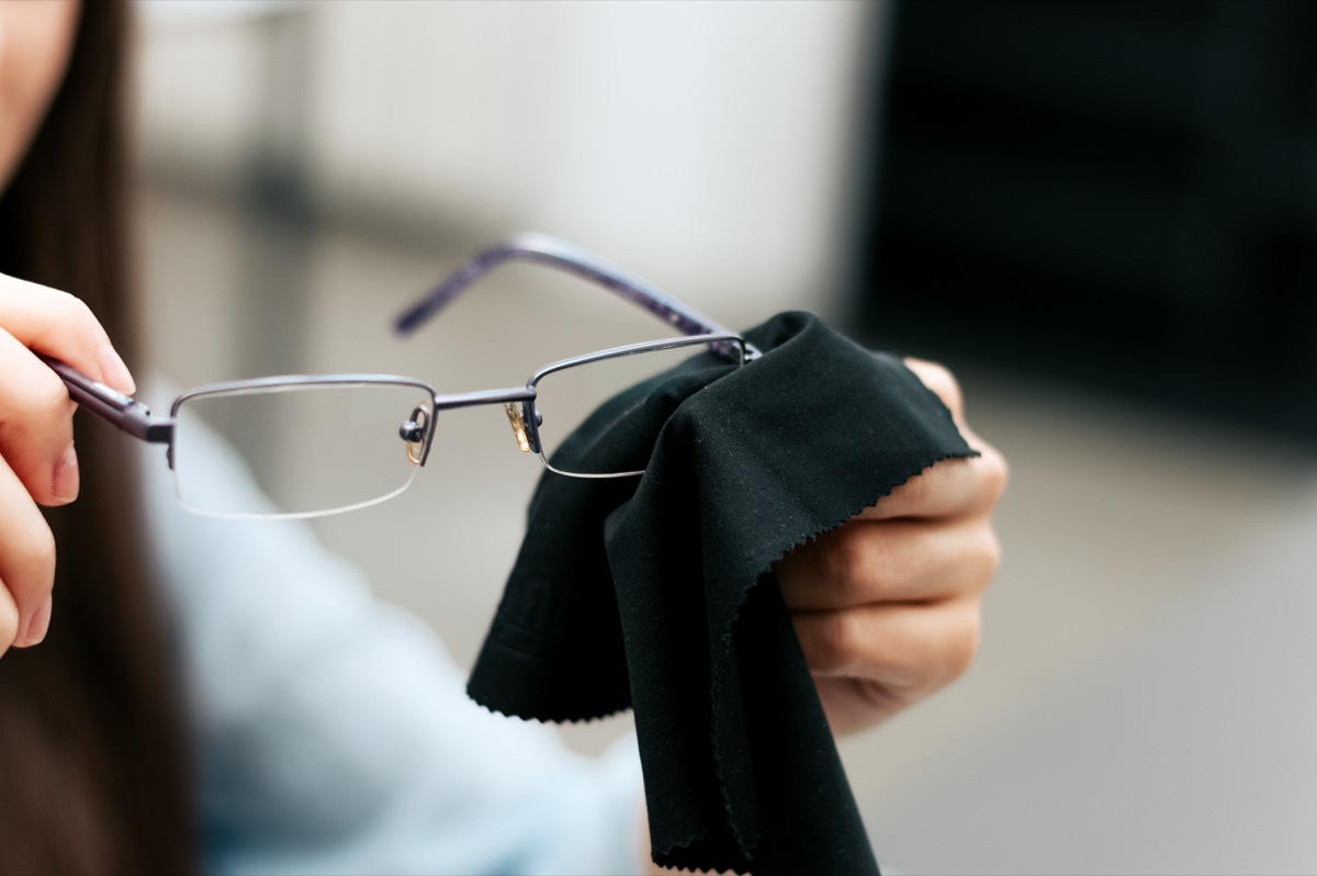 woman cleaning eye glasses with black cloth