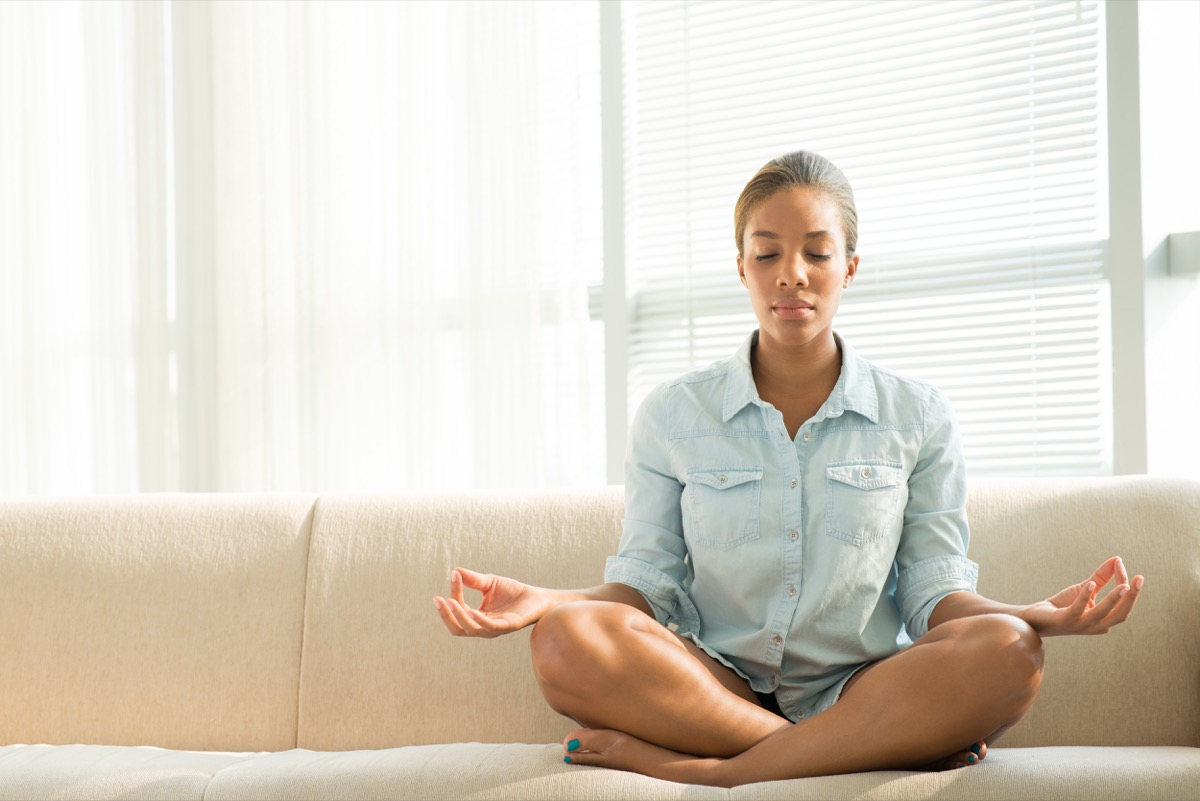 Woman meditating on the couch