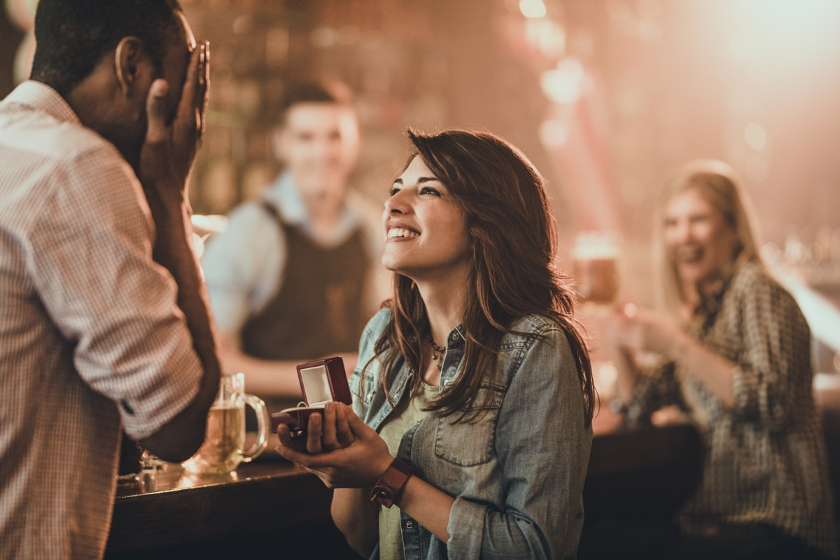 Young happy woman proposing her black boyfriend during night out in a pub. There are people in the background.