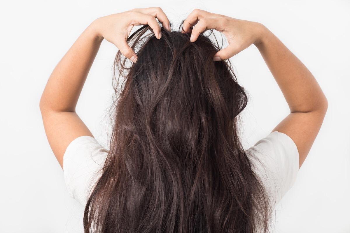 Woman giving herself a scalp massage