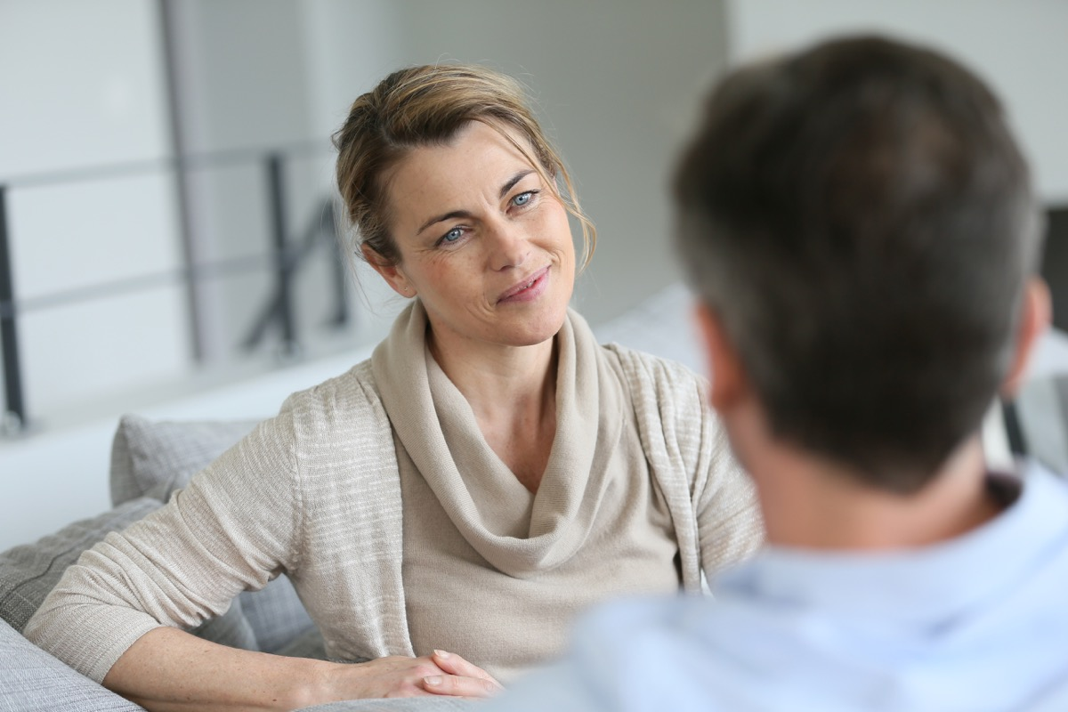 white woman talking to man on couch
