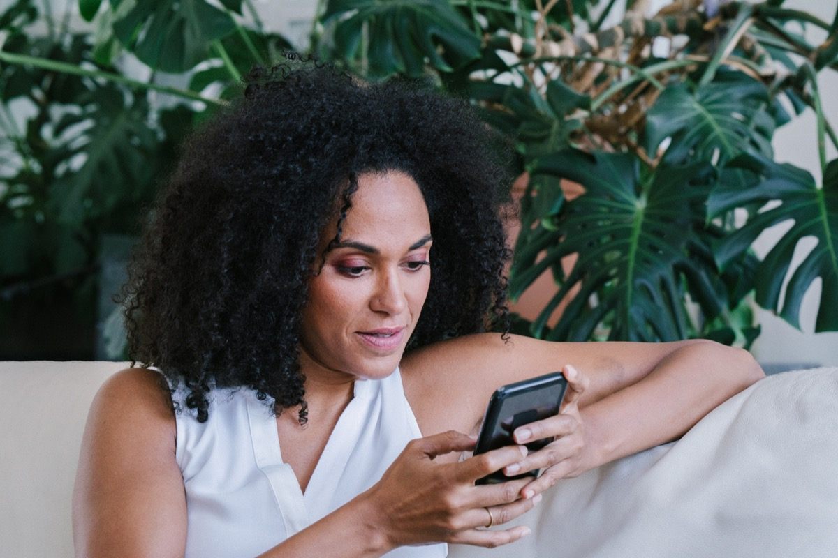serious woman sitting on a sofa texting someone